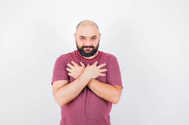 Jonge man hand in hand op de borst in roze t-shirt en ziet er positief uit, vooraanzicht.
