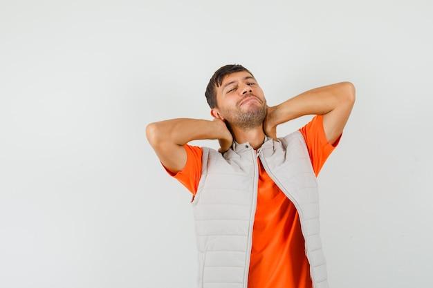Jonge man hand in hand op de nek in t-shirt, jasje en op zoek ontspannen. vooraanzicht.
