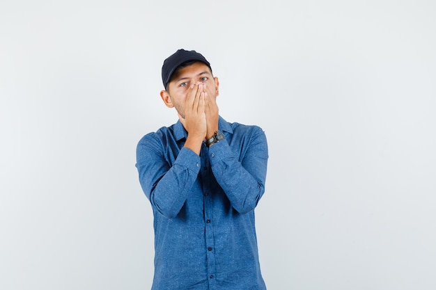 Jonge man hand in hand op gezicht in blauw shirt, pet en ziet er bang uit. vooraanzicht.