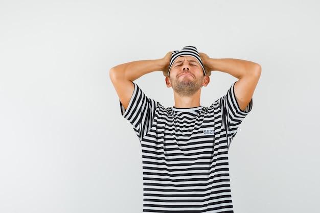 Jonge man hand in hand op het hoofd in gestreepte t-shirt hoed en spijtig op zoek