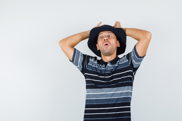 Jonge man hand in hand op het hoofd in t-shirt, hoed en ziet er bang uit. vooraanzicht.