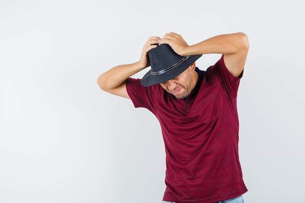 Jonge man hand in hand op het hoofd in t-shirt, hoed en ziet er spijtig uit. vooraanzicht.