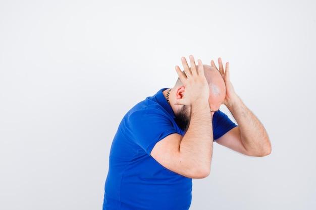 Jonge man hand in hand op het hoofd terwijl hij naar voren buigt in blauw shirt en ongeduldig kijkt. .