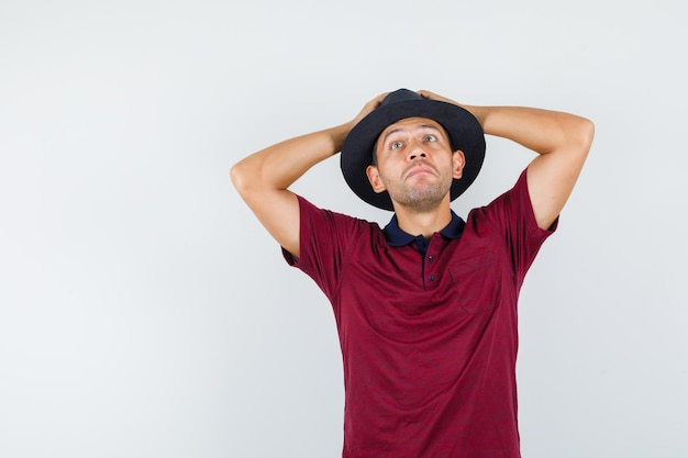 Jonge man hand in hand op hoofd in t-shirt, hoed en verbaasd, vooraanzicht.