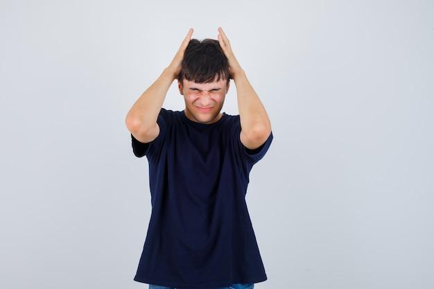 Jonge man hand in hand op hoofd in zwart t-shirt en op zoek geïrriteerd, vooraanzicht.