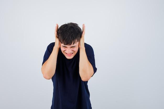 Jonge man hand in hand op oren in zwart t-shirt en op zoek geïrriteerd. vooraanzicht.