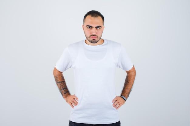 Jonge man hand in hand op taille in wit t-shirt en zwarte broek en serieus kijken