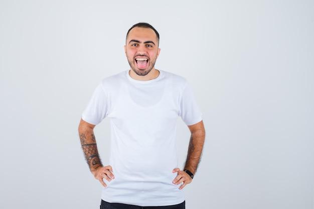 Jonge man hand in hand op taille, tong uitsteekt in wit t-shirt en zwarte broek en er gelukkig uit