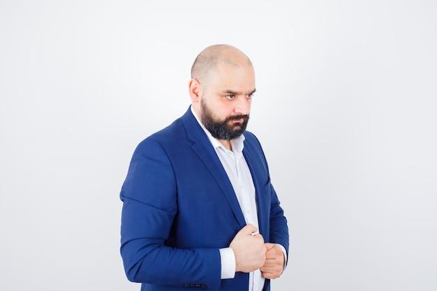 Jonge man hand in hand op zijn jas in wit overhemd, jas en ziet er zelfverzekerd uit. vooraanzicht.