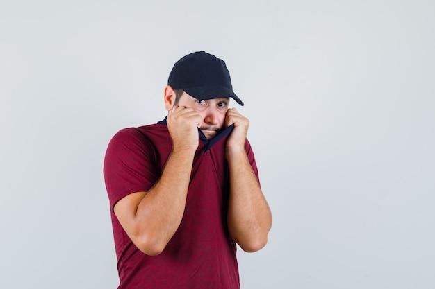Jonge man hand in hand op zijn kraag in rood t-shirt, zwarte pet en bang op zoek. vooraanzicht.