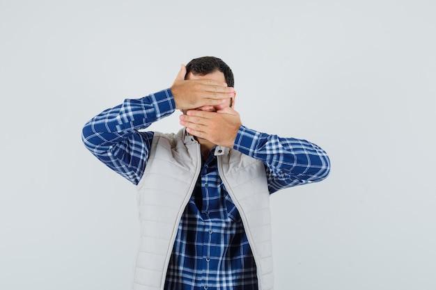 Jonge man hand in hand op zijn ogen, mond in shirt, mouwloos jasje en op zoek verborgen. vooraanzicht.