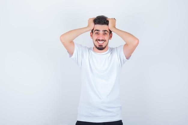 Jonge man hand in hand terwijl hij in t-shirt poseert en er vrolijk uitziet joy