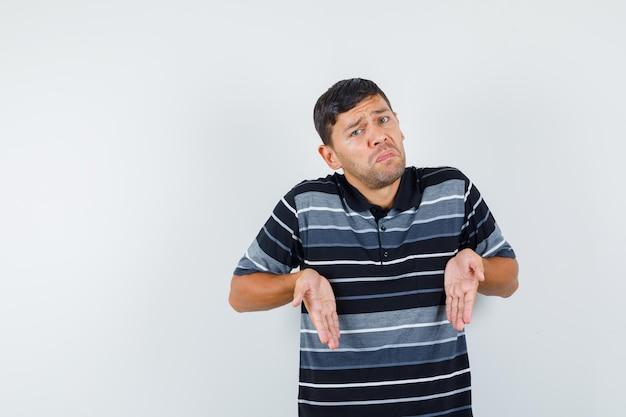 Jonge man hand in hand zoals iets hieronder in t-shirt laten zien en verward kijken. vooraanzicht.