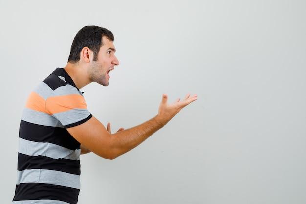 Jonge man hand op agressieve manier in t-shirt verhogen en boos kijken. . ruimte voor tekst