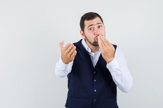 Jonge man hand op de mond houden, wijzend op camera in hemd, vest vooraanzicht.