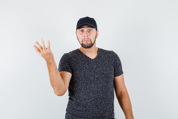 Jonge man hand op hulpeloze wijze in t-shirt en pet opheffen en verward op zoek
