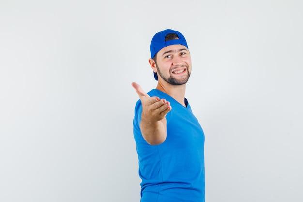 Jonge man hand uitrekken voor schudden in blauw t-shirt en pet en op zoek blij