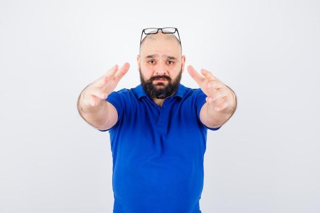 Jonge man handen naar voren uitrekken voor knuffelen in blauw shirt, glazen vooraanzicht.
