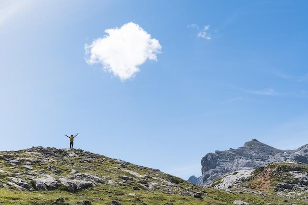 Jonge man handen omhoog op de top van een berg.