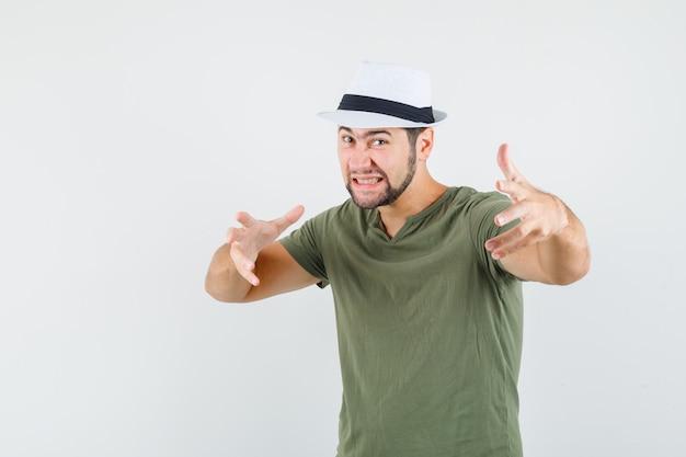 Jonge man handen uitrekken zoals iets in groen t-shirt en hoed grijpen en agressief kijken