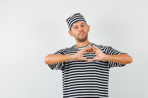 Jonge man hart gebaar in gestreept t-shirt, hoed tonen en er schattig uitzien.