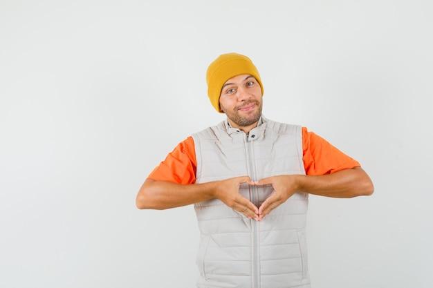 Jonge man hart gebaar tonen en glimlachend in t-shirt, jasje, hoed