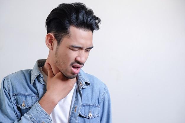 Jonge man heeft een zere keel en raakt zijn nek aan.