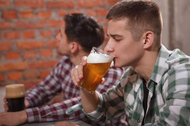 Jonge man heerlijk bier nippen in de pub