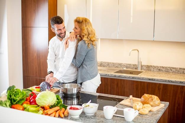 Jonge man helpen zijn vriendin koken in de moderne keuken bekijken