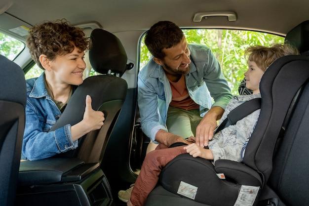 Jonge man helpt zijn schattige zoontje met het vastmaken van de veiligheidsgordel terwijl hij en zijn mooie vrouw de jongen op de achterbank van de auto bekijken