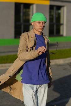 Jonge man herfst kleding dragen in de straat. jonge kerel die zonnebril houdt en jas, en groene hoed draagt