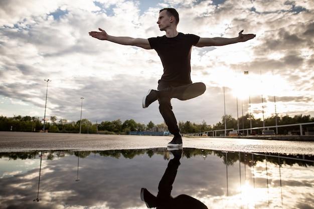 Jonge man het beoefenen van yoga op een achtergrond van blauwe hemel met wolken na regen. buiten mediteren. yoga, sport, gezonde levensstijl