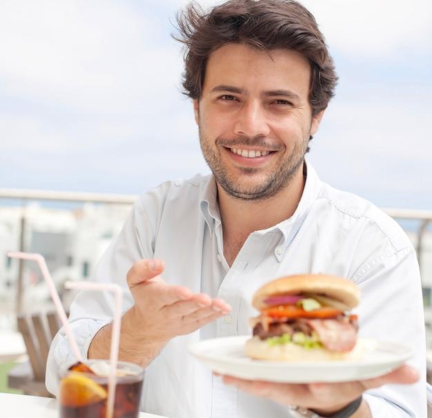 Jonge man het eten van een hamburguer