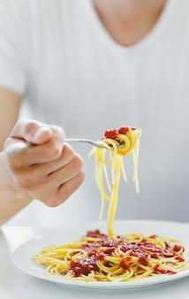 Jonge man het eten van smakelijke spaghetti met tomatensaus. detailopname.