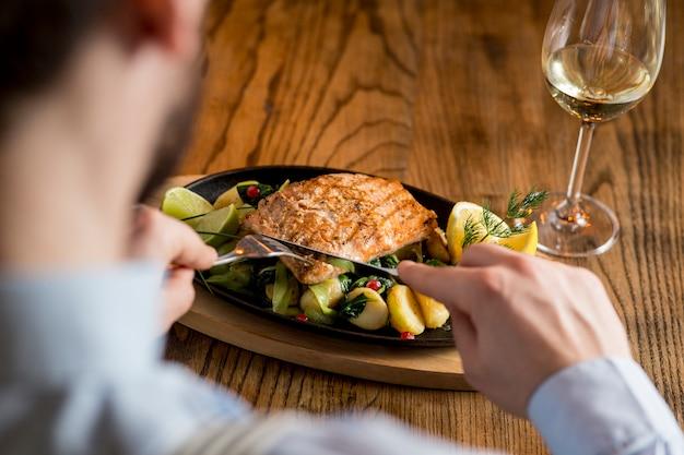 Jonge man het eten van zalmfilet met gegratineerde aardappelen, prei en spinazie