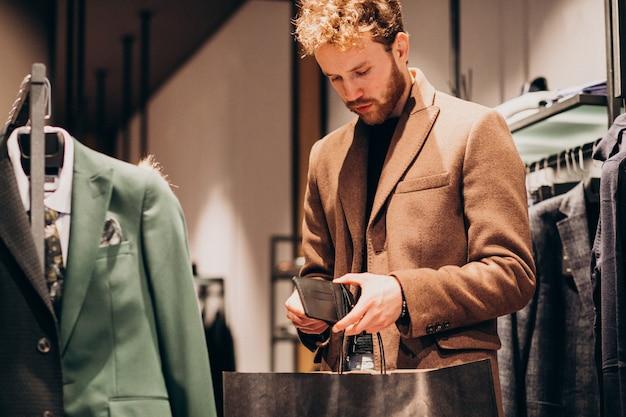 Jonge man het kopen van kleding en betalen met contant geld bij een winkel