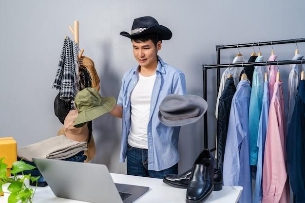 Jonge man hoed en kleding online verkopen via live streaming van smartphone. zakelijke online e-commerce thuis