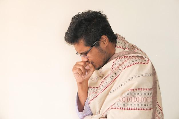 Jonge man hoest en niest tegen witte muur