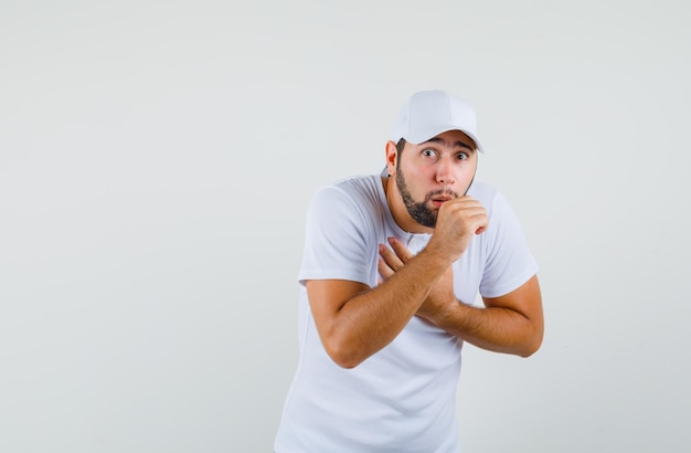 Jonge man hoest in t-shirt, pet en ziet er ziek uit, vooraanzicht.