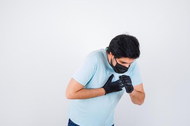 Jonge man hoest terwijl hij in een t-shirt staat en er onwel uitziet. vooraanzicht.