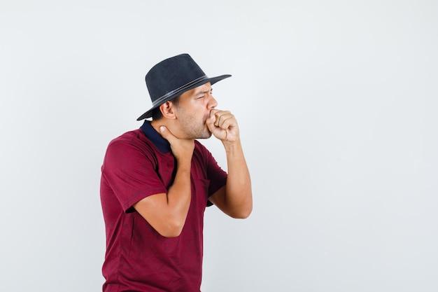 Jonge man hoest vanwege keelpijn in t-shirt, hoed en ziet er ziek uit. vooraanzicht.