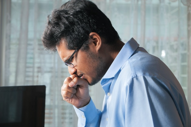 Jonge man hoesten tijdens het werken op laptop