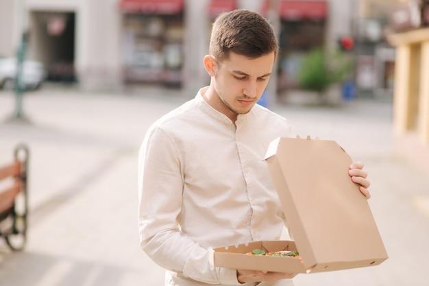 Jonge man honger lijden tijdens het openen van pizzadoos buitenshuis