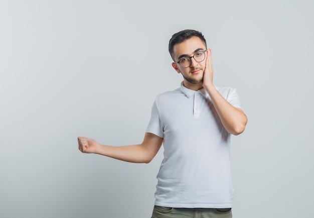 Jonge man houdt de hand op de wang, wijst weg in wit t-shirt, broek en kijkt verstandig