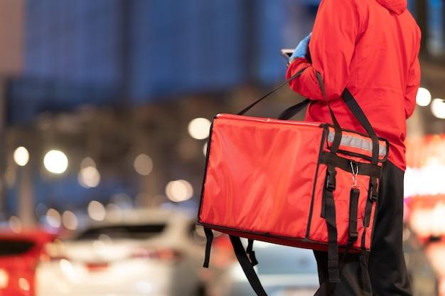Jonge man houdt een grote rode zak vast die voor een voedsellevering werkt