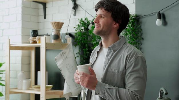 Jonge man houdt een mok koffie vast en kijkt uit het raam