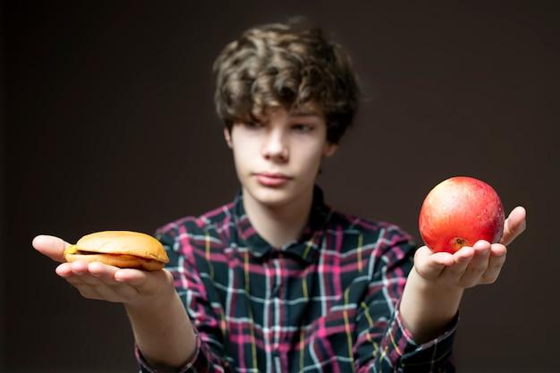 Jonge man houdt en kiest tussen appel of hamburger b
