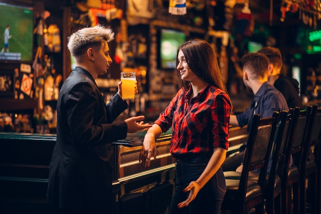 Jonge man houdt glas bier in de hand en praat met vrouw aan de toog in een sportcafé, gelukkige vrije tijd van voetbalfans