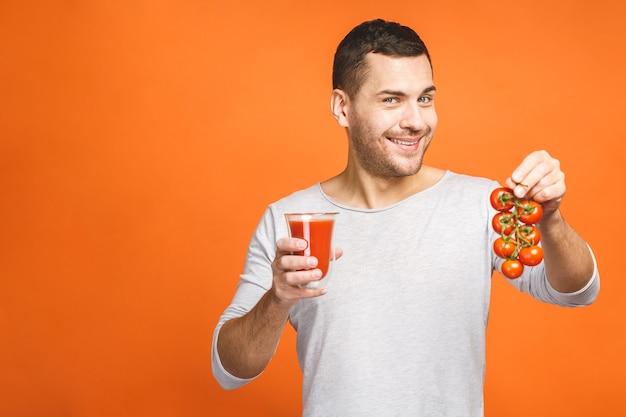 Jonge man houdt glas sap en eet groenten geïsoleerd op een oranje achtergrond