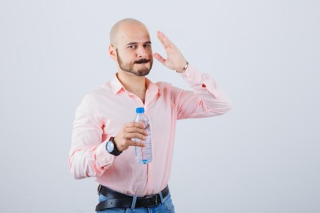 Jonge man houdt hand in de buurt van gezicht in shirt, spijkerbroek en ziet er serieus uit, vooraanzicht.
